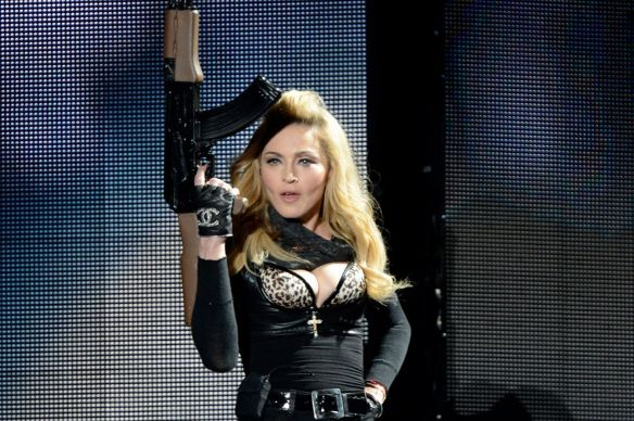 Madonna performs with an AK machine gun on stage during her